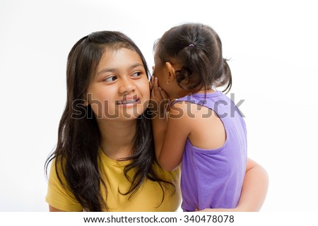 Asian Child Whispering Something to Teen Sister Isolated on White - stock photo
