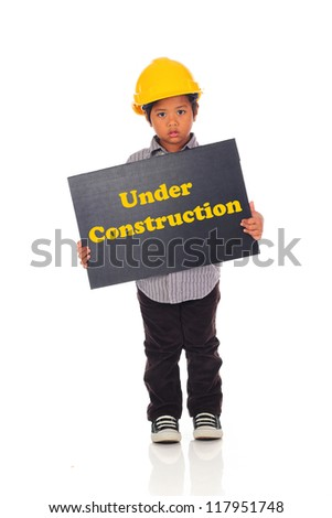 Asian child with a yellow helmet and text Under Construction Board isolated on a over white background - stock photo