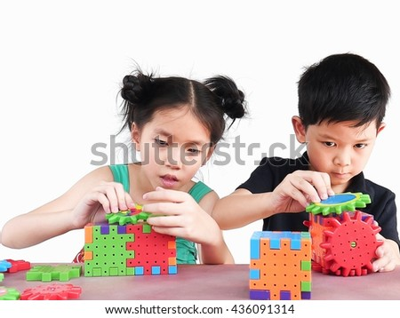 Asian children are playing puzzle plastic block creative game to practice their physical and mental skill - stock photo