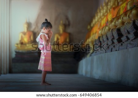 Asian children in Thai traditional dress of Buddhism worshiping Buddha statue with faith at Ayutthaya historical park of Ayutthaya Province, Thailand