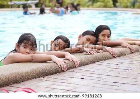 Asian children lining up at the pool side. - stock photo
