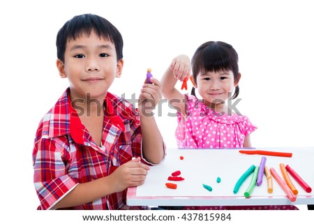 Asian children playing and creating toys from play dough. Boy and girl smiling and show works from clay at camera, on white background. Strengthen the imagination of child - stock photo