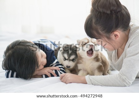 Asian children playing with puppies on white bed