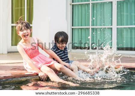 Asian children splashing around in the pool - stock photo