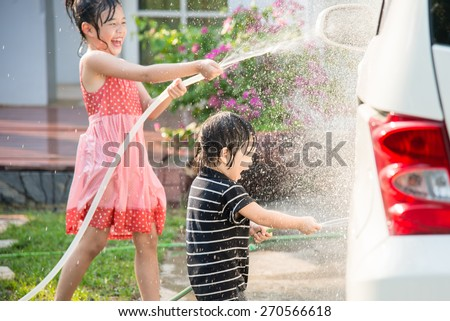 Asian children washing car in the garden - stock photo