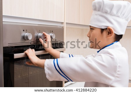 Asian Chinese Boy in white chef uniform Baking Cookies at Home