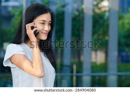 asian chinese businesswoman office worker communicating with mobile phone - stock photo