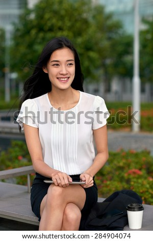 asian chinese businesswoman office worker communicating with tablet computer on coffee break outdoors - stock photo