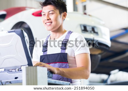 Asian Chinese car mechanic checking auto engine with diagnostics tool in his workshop