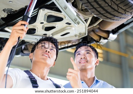 Asian Chinese car mechanic with customer looking at auto floor with lamp - stock photo