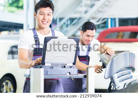 Asian Chinese car mechanics checking auto engine with diagnostics tool in his workshop - stock photo