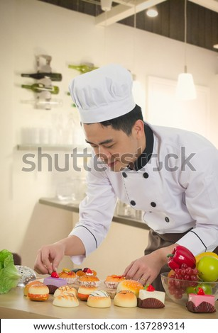 asian chinese chef preparing foods for his customer with kitchen background - stock photo