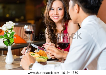 Asian Chinese couple - Man and woman - or lovers flirting and having a date or romantic dinner in a fancy restaurant  - stock photo