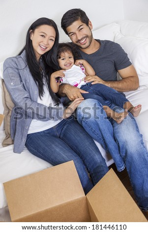Asian Chinese family, parents and young girl child daughter, packing or unpacking boxes and moving into a new home. - stock photo