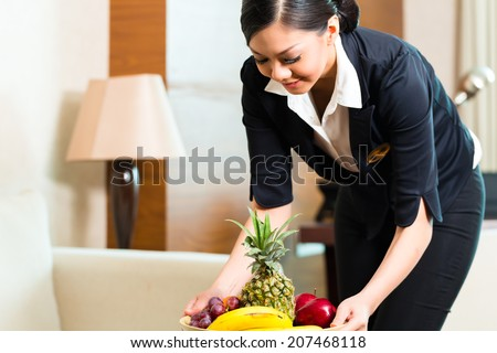 Asian Chinese hotel executive housekeeper placing fruit treatment to welcome arriving VIP guests  - stock photo