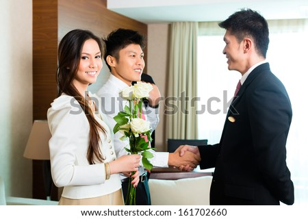 Asian Chinese Hotel Manager or director or supervisor welcome arriving VIP guests with roses on arrival in luxury or grand hotel - stock photo