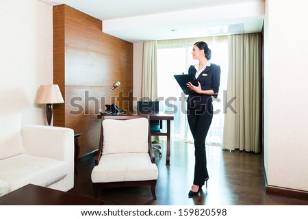 Asian Chinese Housekeeping manager or assistant controlling or checking the room or suit of a hotel with a checklist on tidiness  - stock photo