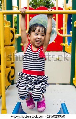 Asian Chinese little girl hanging on outdoor playground - stock photo