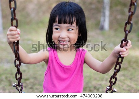Asian Chinese little girl on swing in playground outdoor.