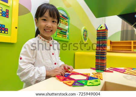 Asian Chinese little girl playing colorful magnet plastic blocks kit at indoor playground
