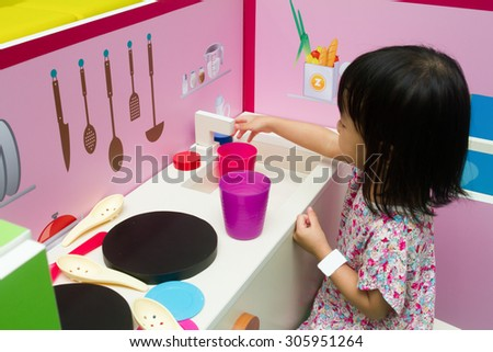 Asian Chinese little girl role-playing at kitchen. - stock photo