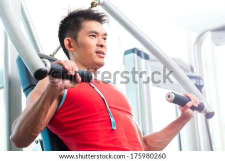 Asian Chinese man having fitness training or workout in gym doing sport to build up muscle on a weight machine - stock photo