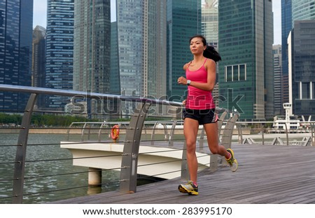 asian chinese sporty woman working out running outdoors along urban city harbor sidewalk morning - stock photo