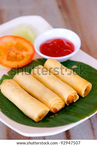 Asian chinese spring rolls with chili sauce and slice of tomato - stock photo