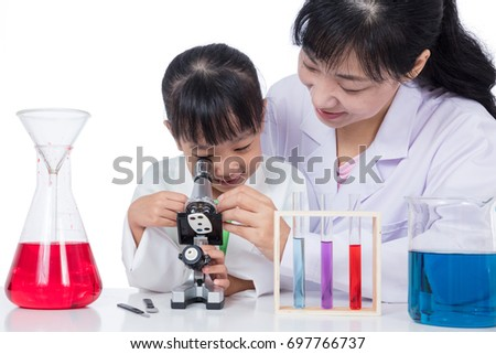 Asian Chinese teacher and little student girl working with microscope in isolated white background