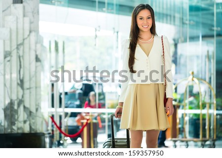 Asian Chinese woman arriving at luxury hotel in business clothes with trolley entering through a glass door into lobby - stock photo