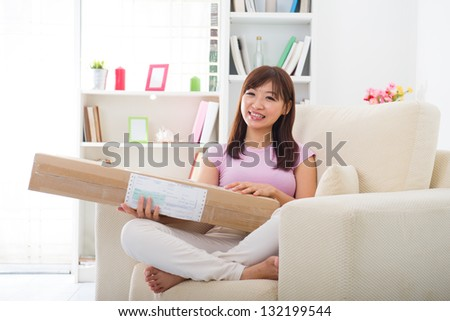 asian chinese woman receiving an online shopping package delivery from a courier at her home.