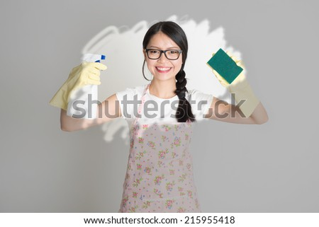 Asian Chinese young woman housewife, spraying detergent and wiping over dirty glass.