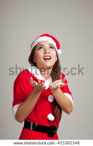 Asian Christmas girl with Santa Claus clothes on gray background