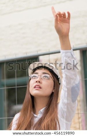 Asian civil engineer wearing protective clothes at work pointing to something above her - stock photo