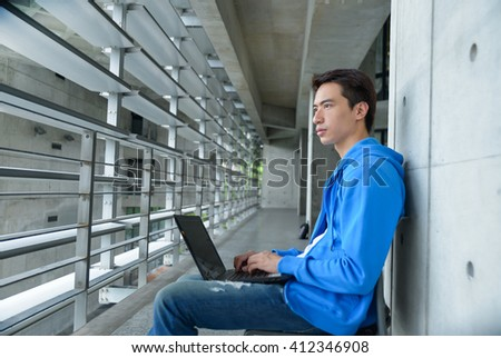Asian college student sitting holding laptop on campus - stock photo