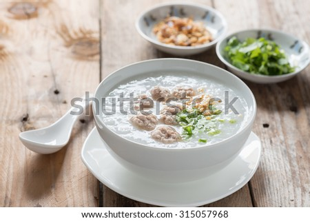 Asian congee with minced pork in white bowl.