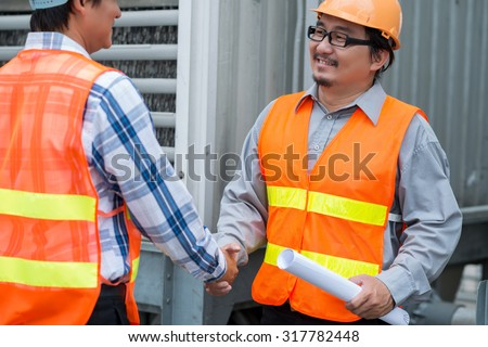 Asian contractor shaking hand of his colleague