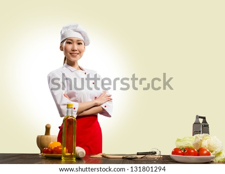 Asian cook woman crossed her arms and smiles - stock photo