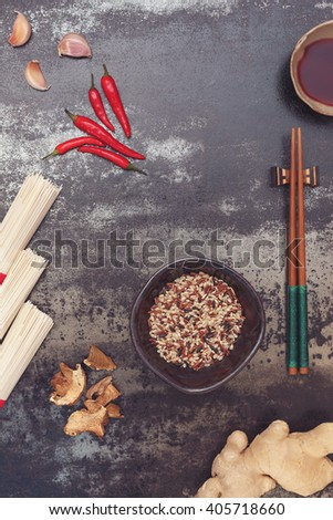 Asian cooking ingredients. Spicy Asian cooking ingredients and sauces with chopsticks on dark background. Top view, vintage toned image, blank space - stock photo