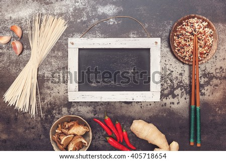 Asian cooking ingredients  with chopsticks on rustic  board, blank blackboard for text. Top view, blank space  - stock photo