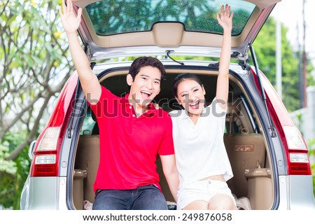 Asian couple buying new car, cheering and sitting in luggage trunk   - stock photo