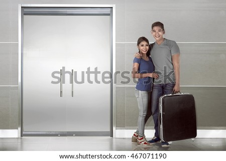 Asian couple carryng suitcase and smile selfie