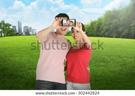 Asian couple doing selfie on city park. Couple travel concept - stock photo