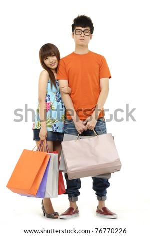 Asian couple doing shopping and carrying shopping bags - stock photo
