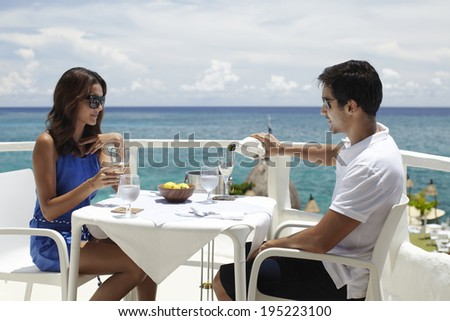Asian couple drinking wine at the sea