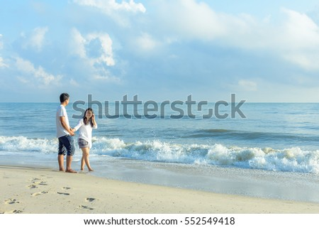 Asian couple enjoy honeymoon on the beach