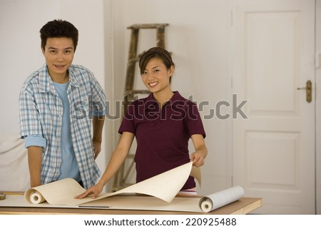 Asian couple hanging wall paper