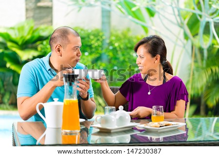 Asian couple having coffee on the porch in front of their home, in the background a tropical garden