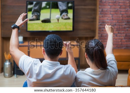 Asian Couple having fun watching golf game in living room - stock photo