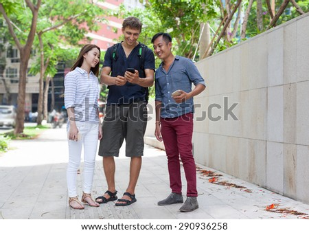 Asian couple help tourist cell smart phone caucasian man mix race friends outdoor city street - stock photo